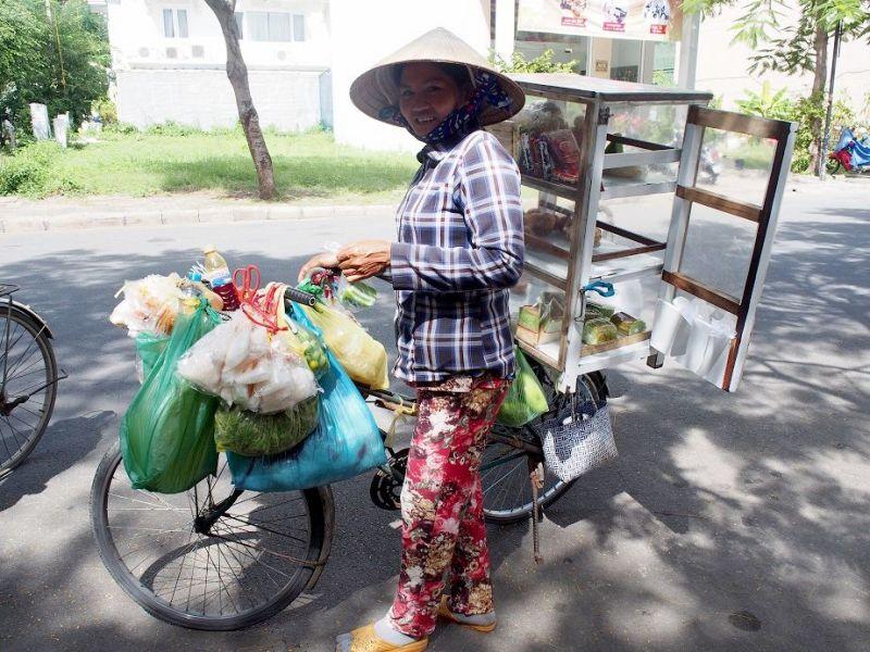 自転車をひいておやつを売るノンラー姿のお姉さん